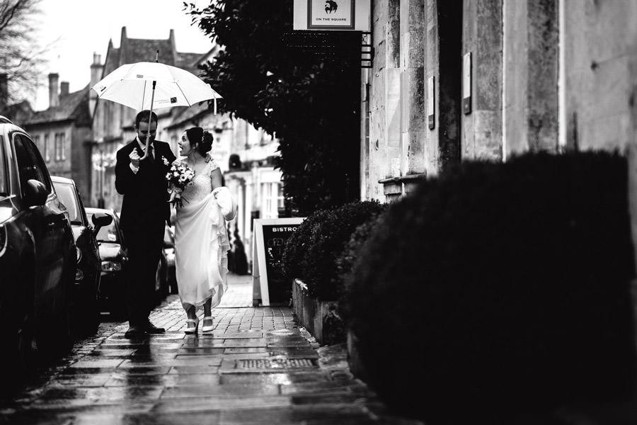 wedding couple walking down the street in rain