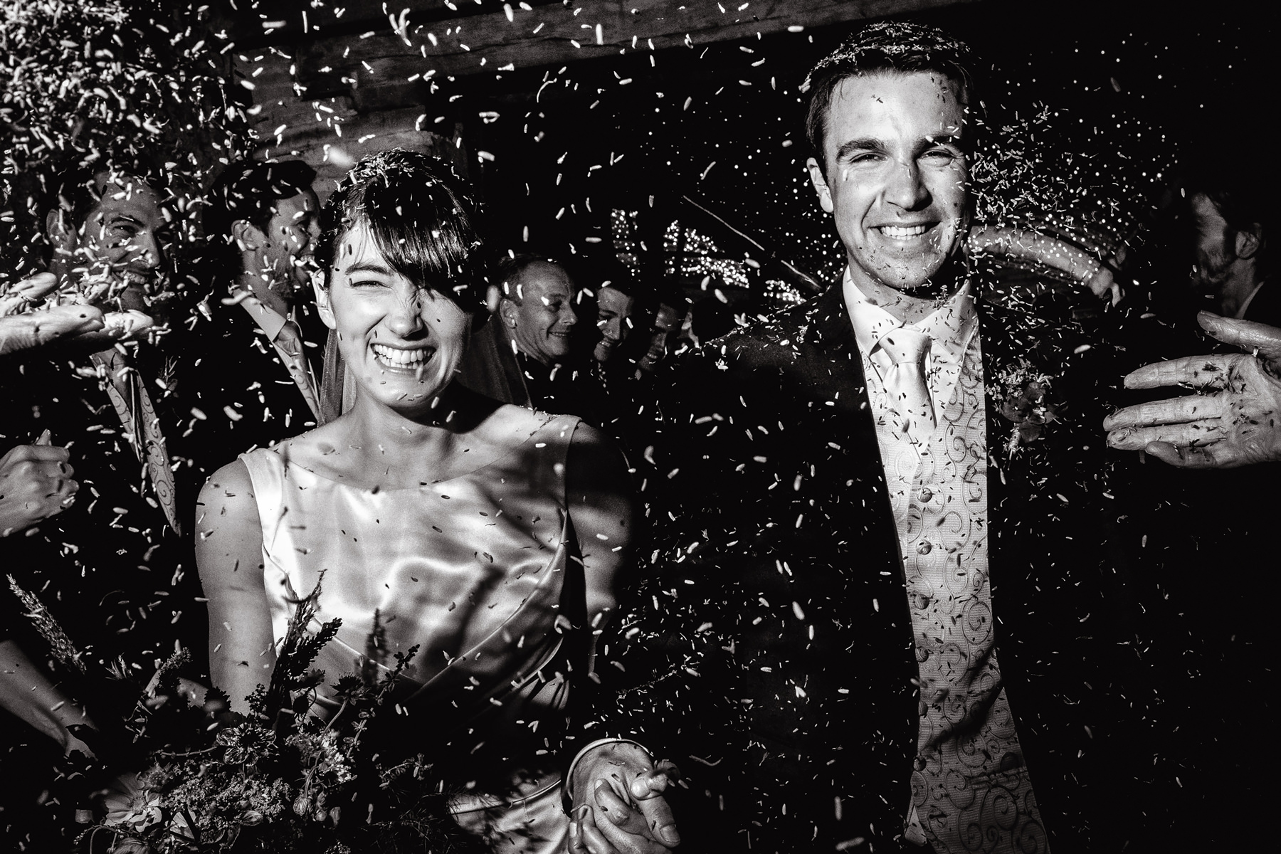 black and white photography of confetti bride and groom