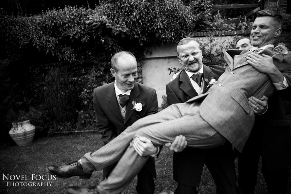 groomsman struggling to lift groom at wedding reception