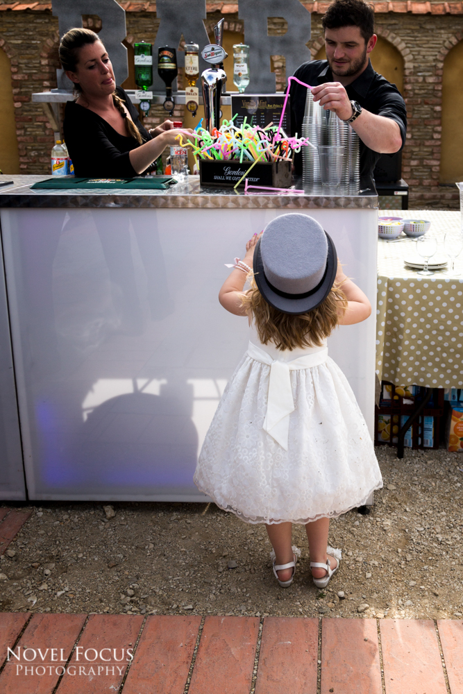 little girl at bar in wedding reception wearing a hat