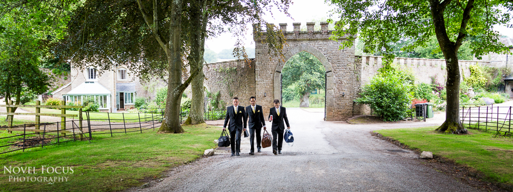 groomsmen walking down path at clearwell castle on wedding day