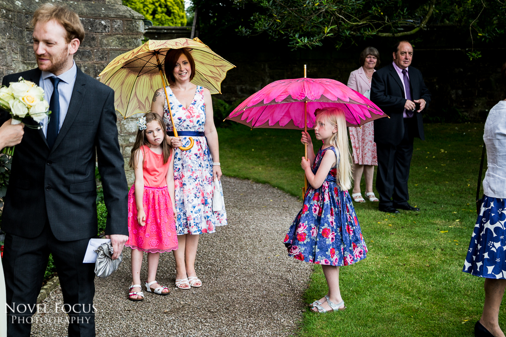 girls with umbrellas looking bored at wedding reception