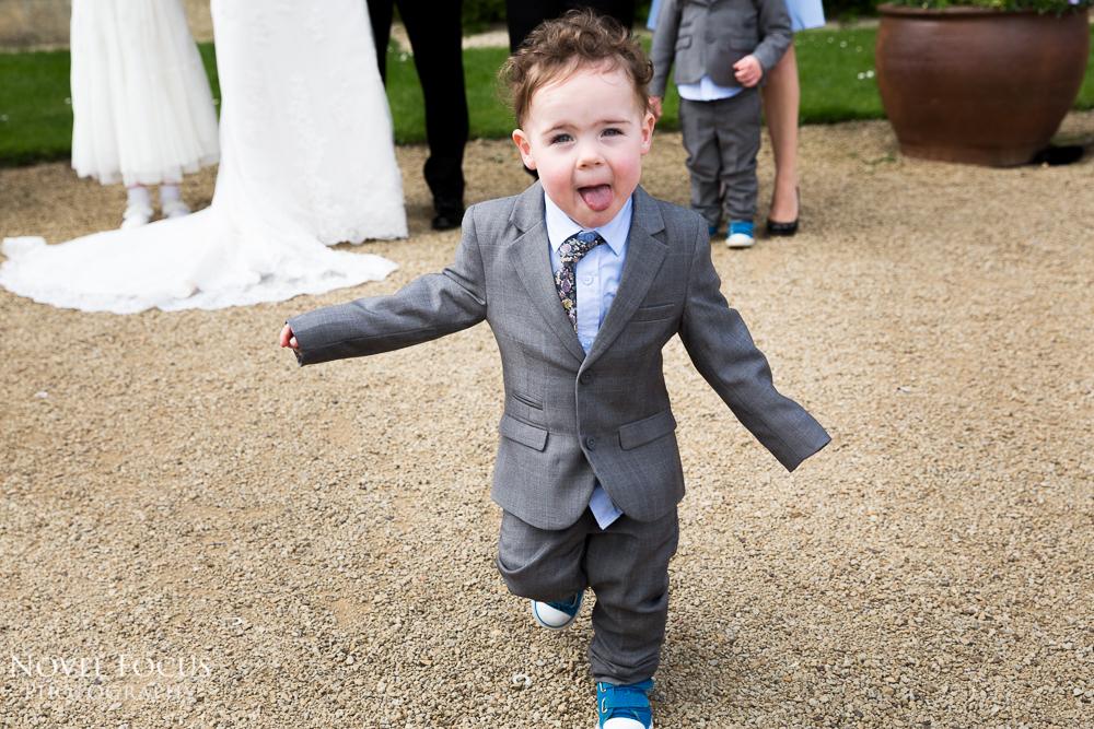 child running towards camera wedding at manor by the lake cheltenham