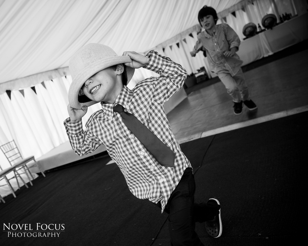 boy running away at wedding reception with hat