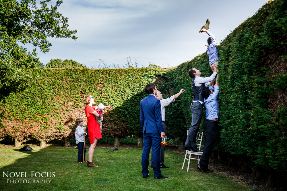boy getting boot from hedge at wedding reception