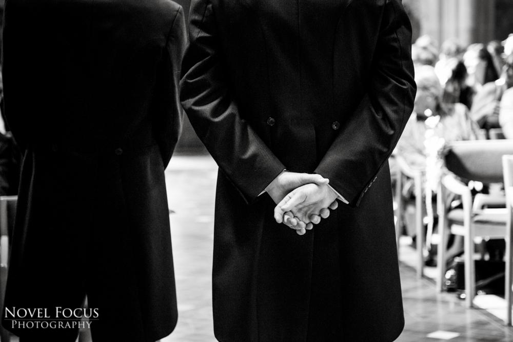 groom holding hands behind back at wedding ceremony