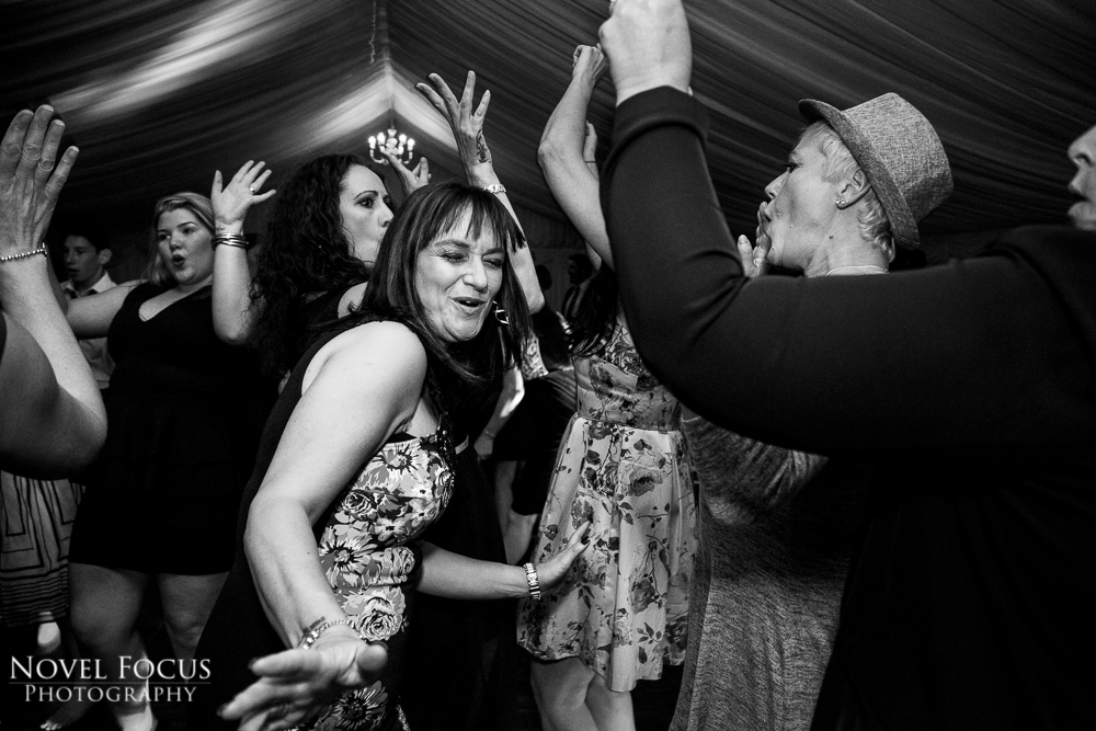 reportage black and white wedding photography of guests dancing