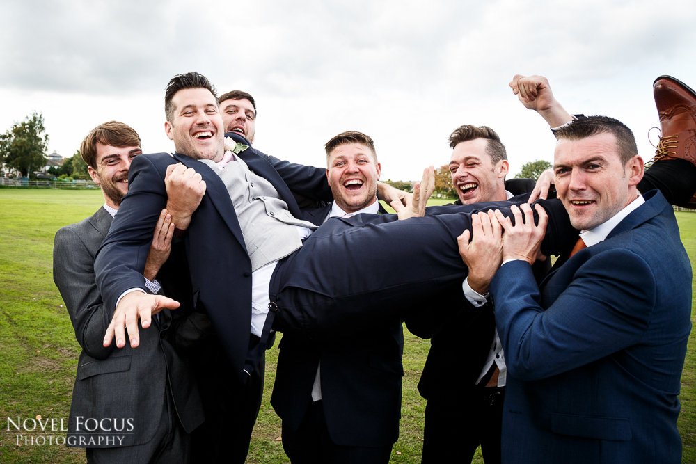 groom being lifted by groomsmen