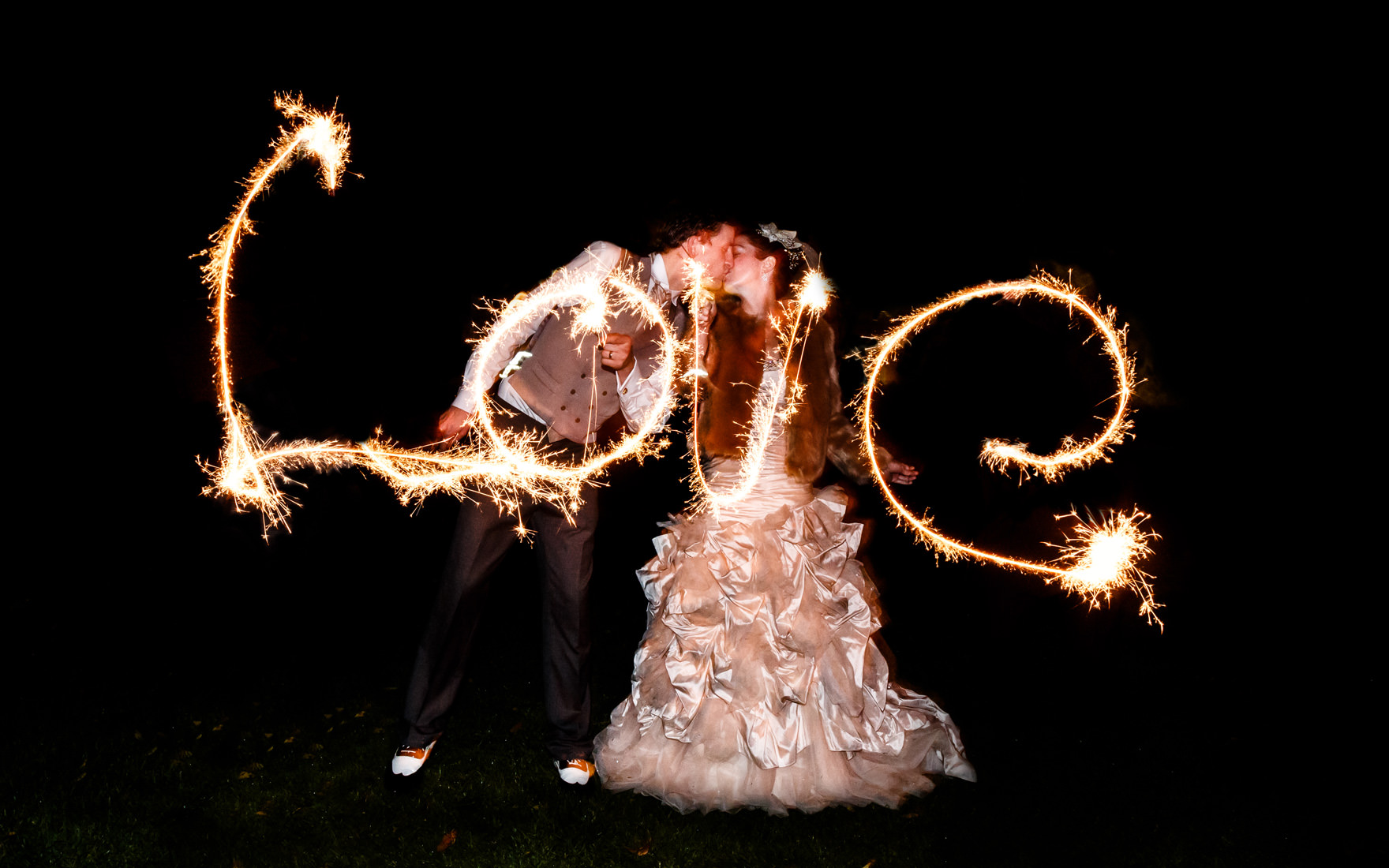 bride and groom spelling love with sparklers at wedding