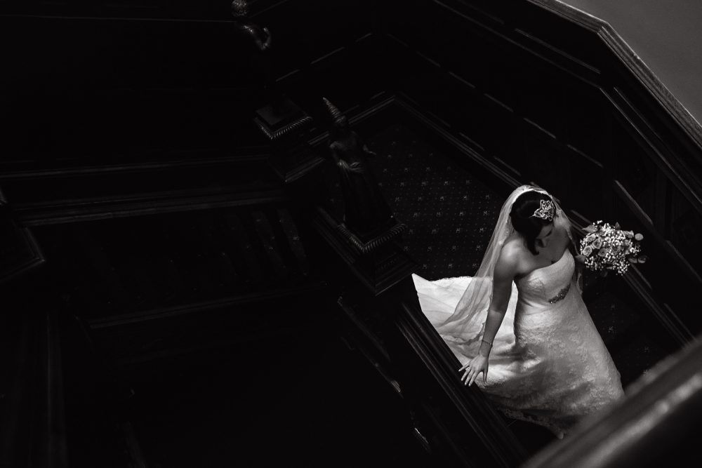 wedding at manor by the lake in cheltenham bride walking down stairs