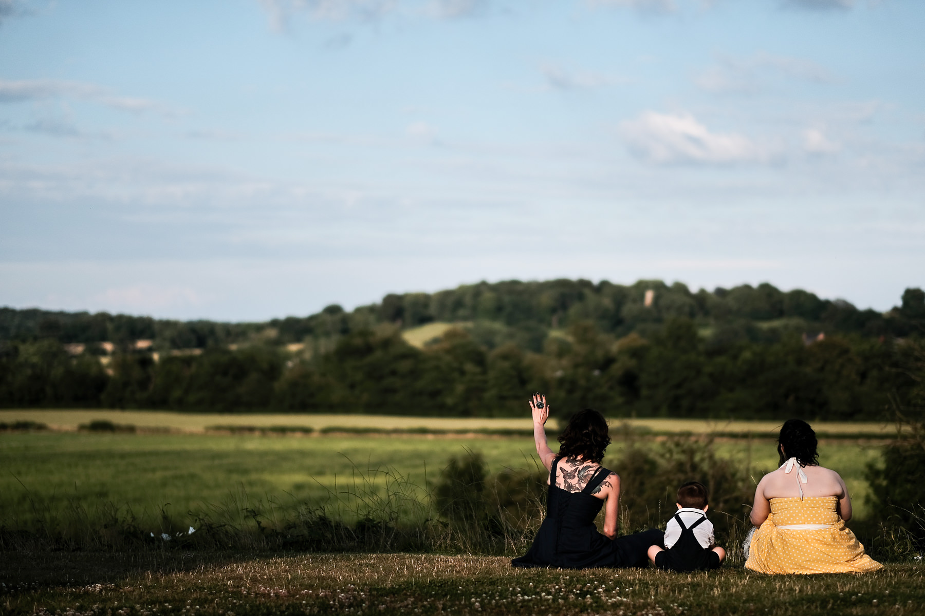 people sat on hill at wedding reception