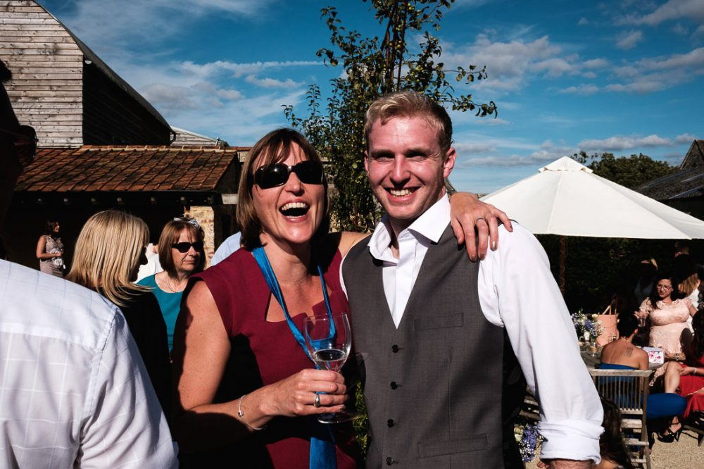 wedding guests enjoying the reception at oxleaze barn burford
