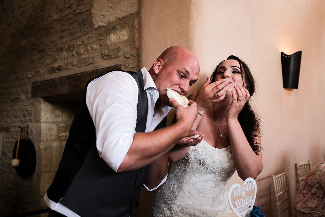 bride and groom laughing as they eat cake