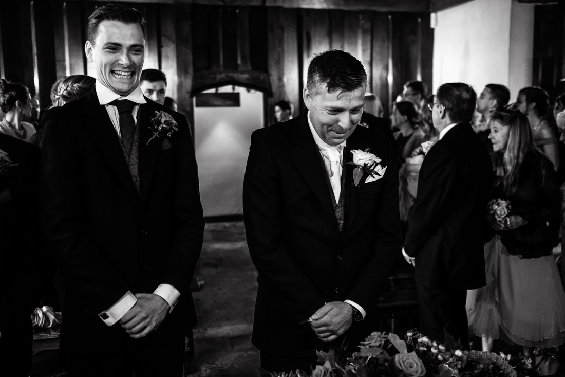 black and white reportage groomsmen waiting in ceremony