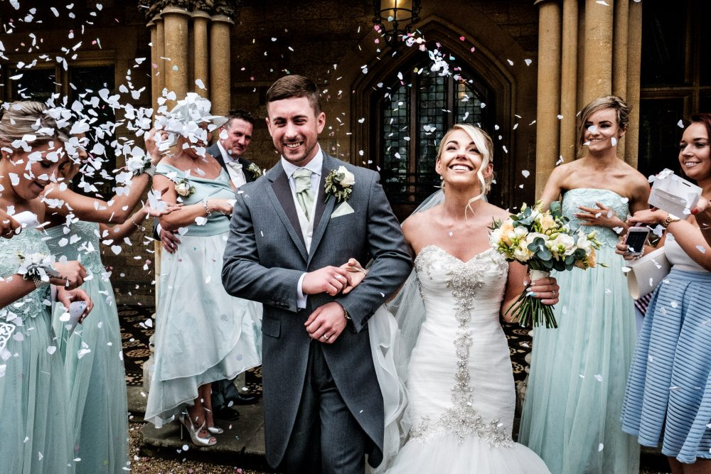 happy bride and groom walking through confetti line on wedding day