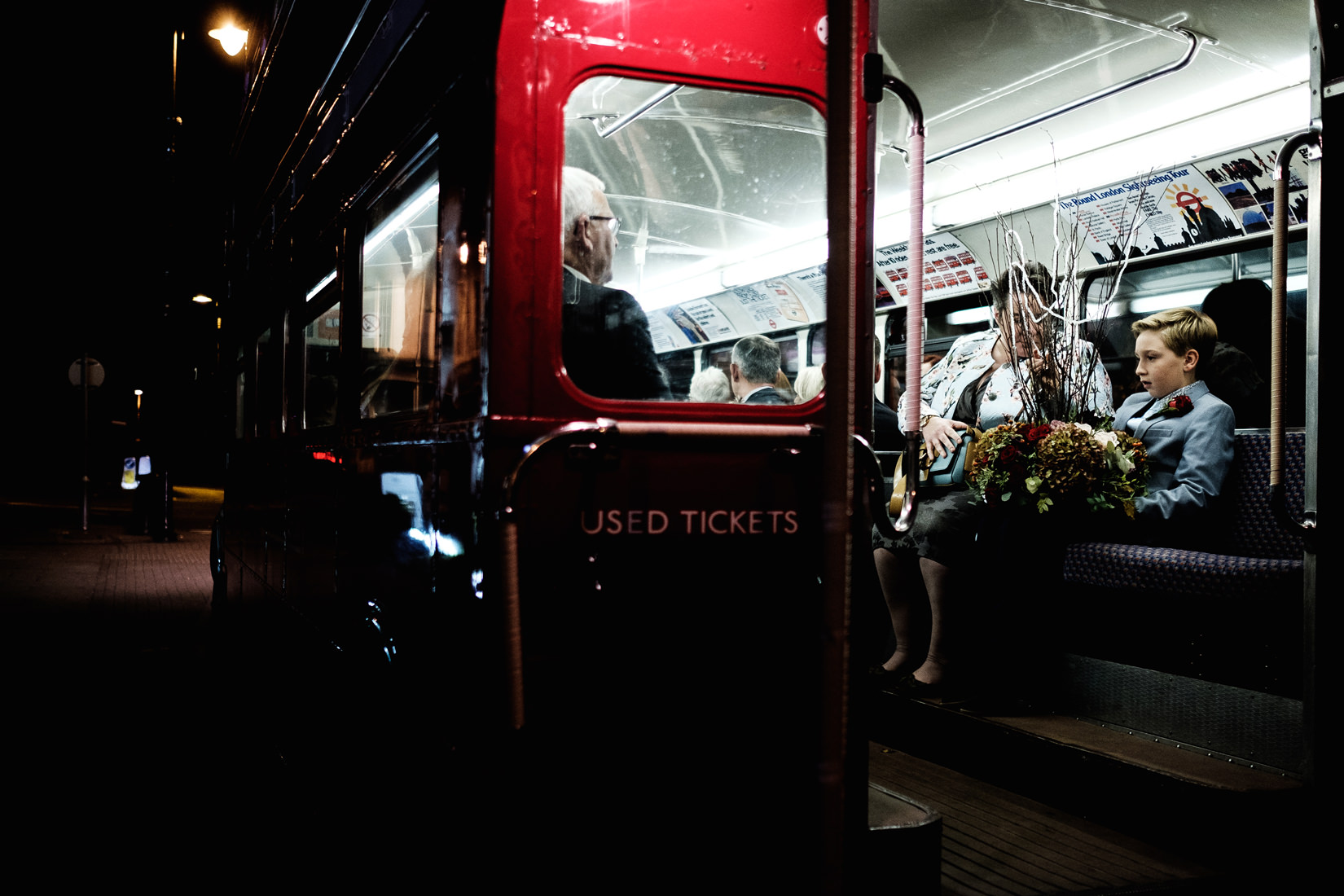 boy on london bus with wedding centrepiece