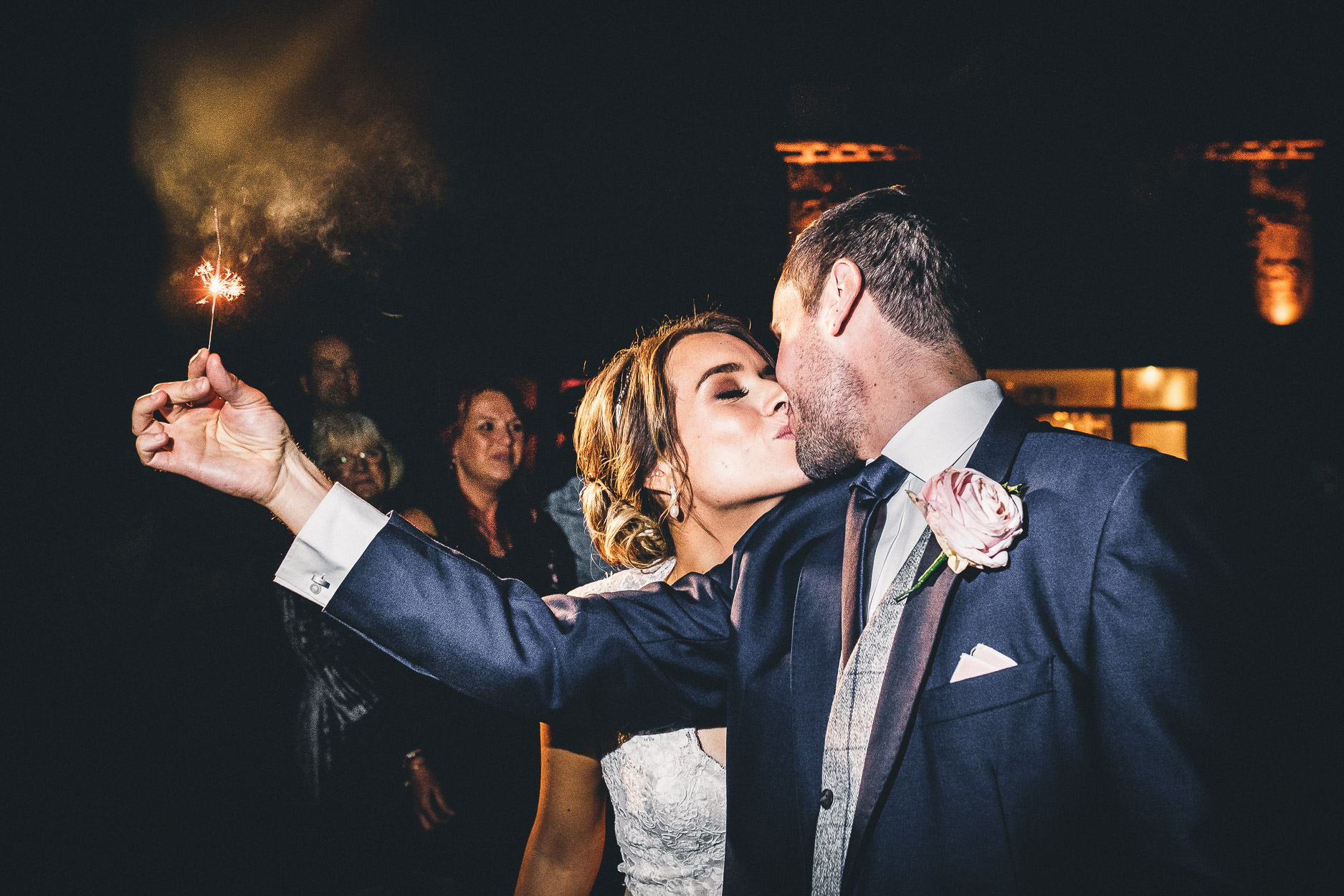 bride and groom holding sparkler at manor by the lake