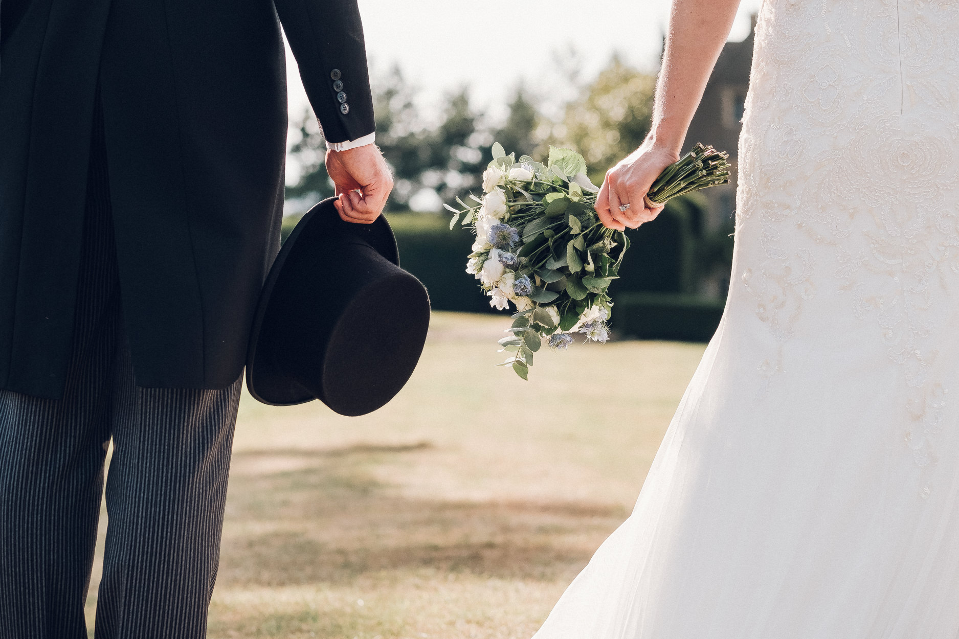 bride holding bouquet groom holding hat
