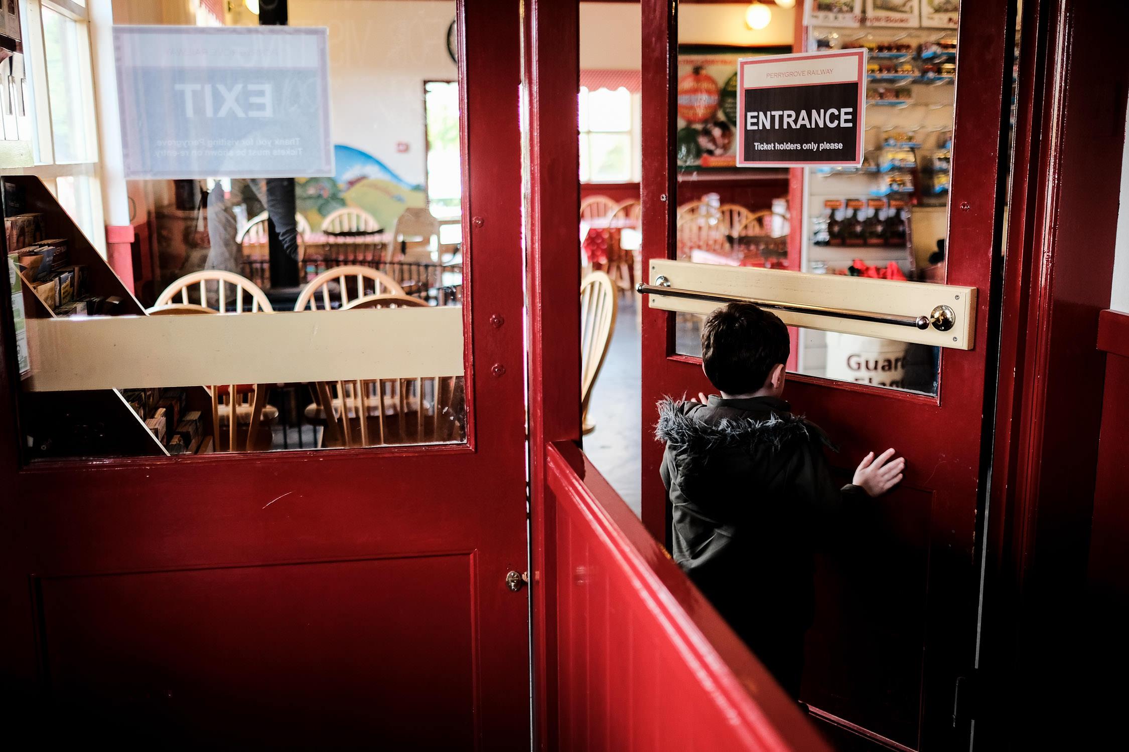 little boy going through red door