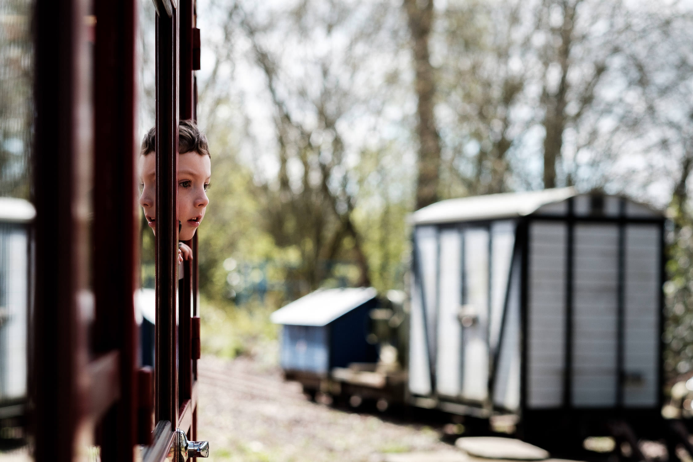 boy with head out of window on train