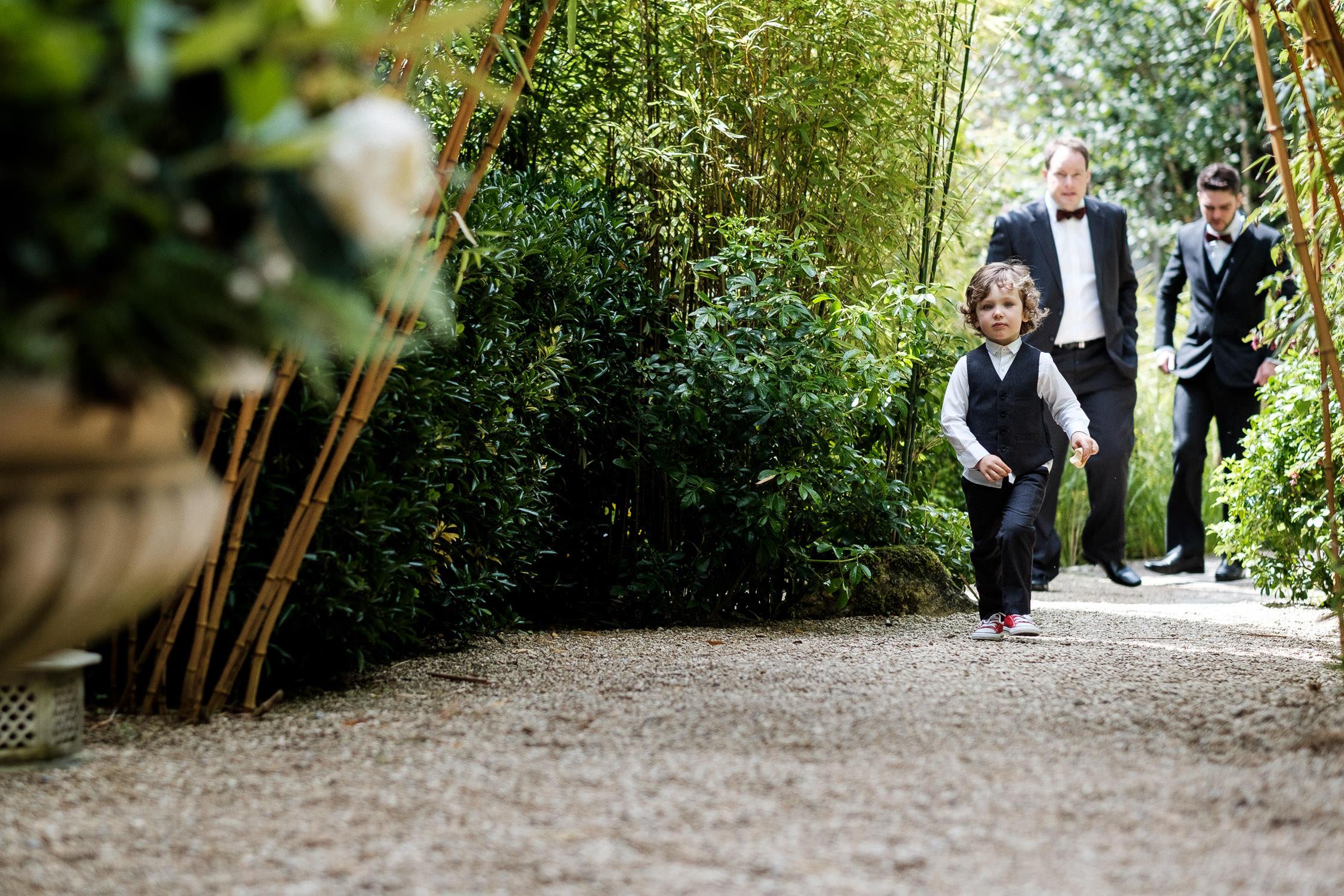 wedding page boy walking through bamboo