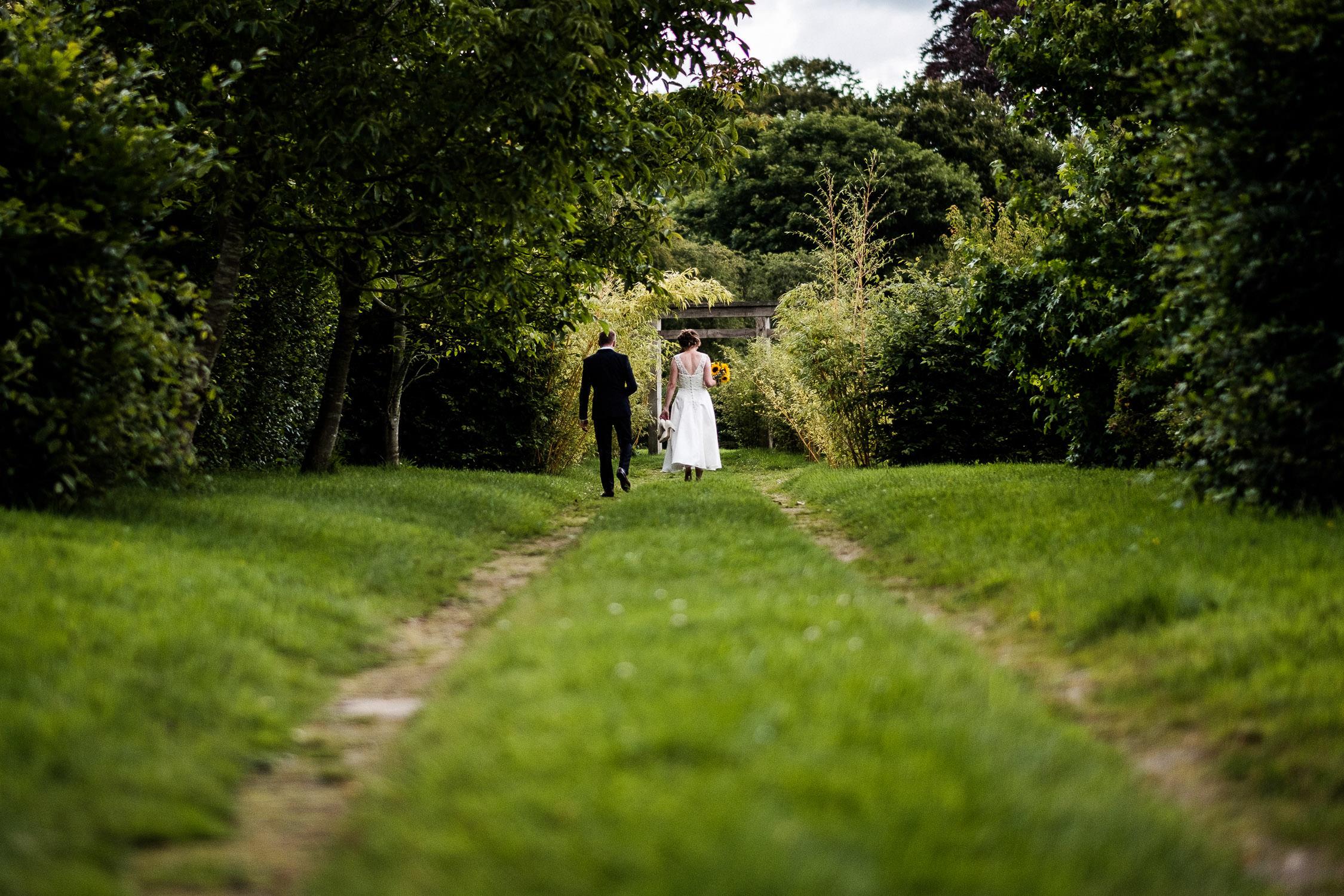 wedding couple walking down path