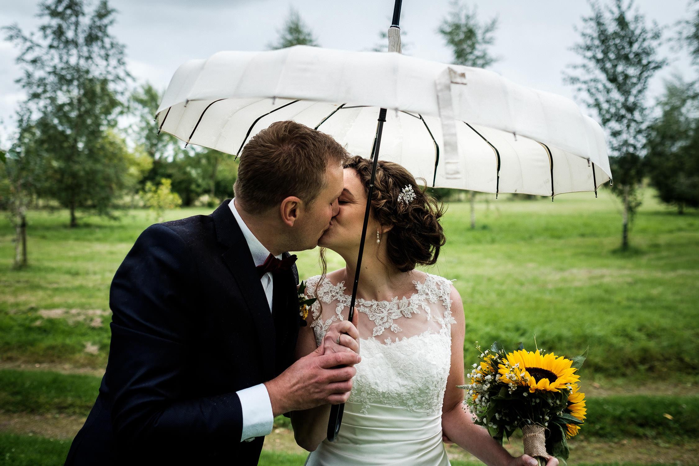 wedding couple share kiss under umbrella
