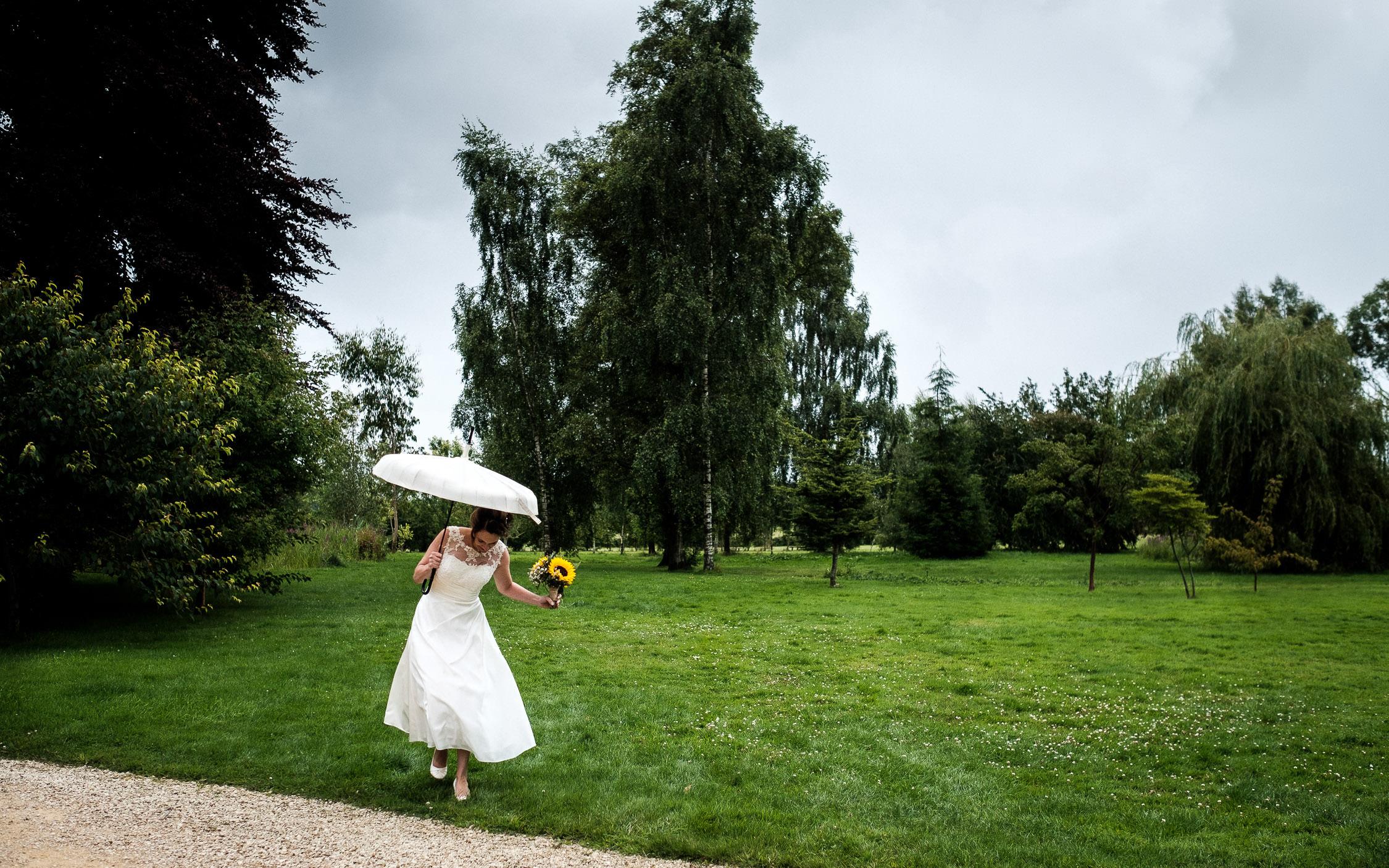 bride walking across field in rain