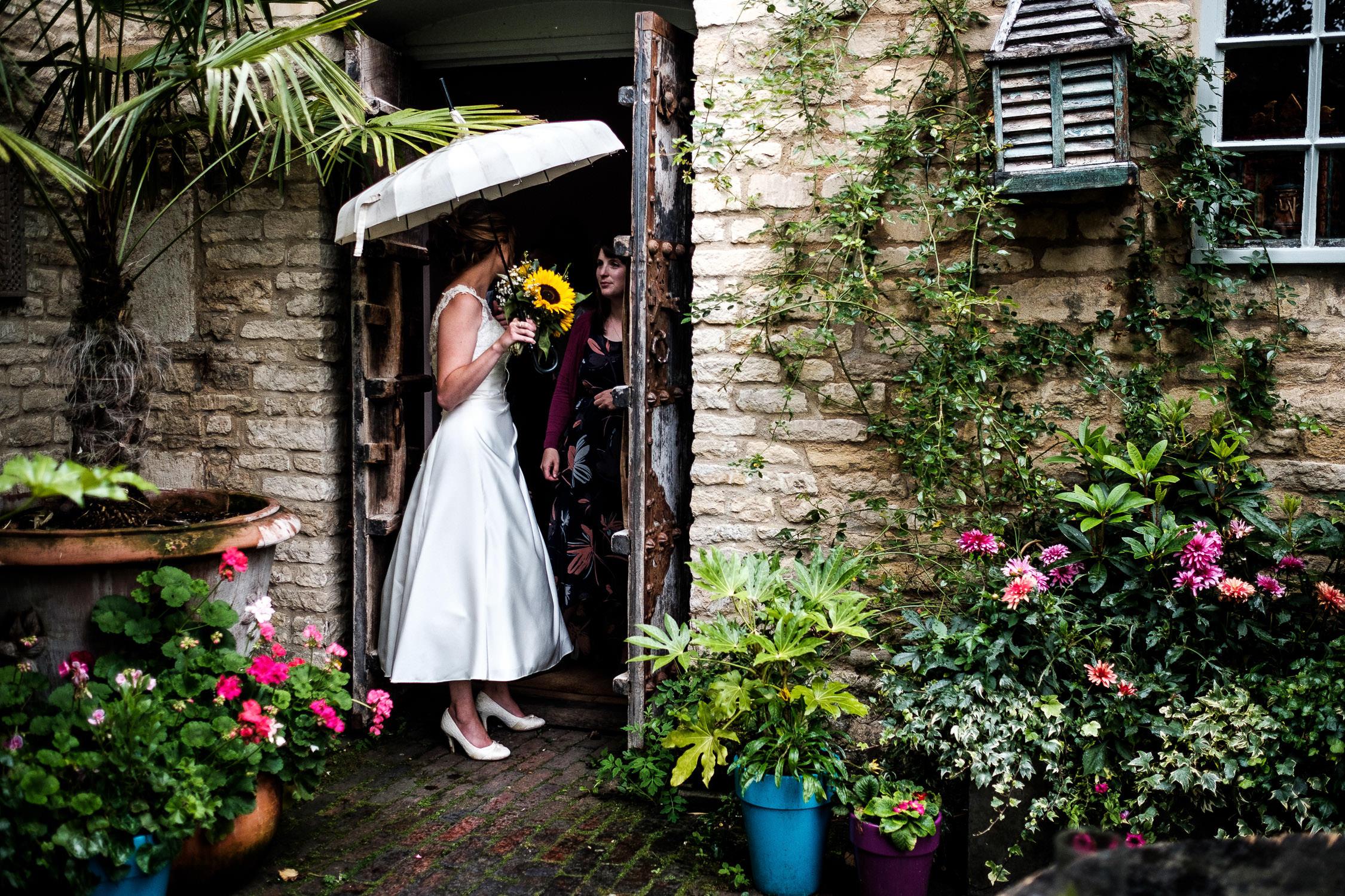 bride standing outside under umbrella
